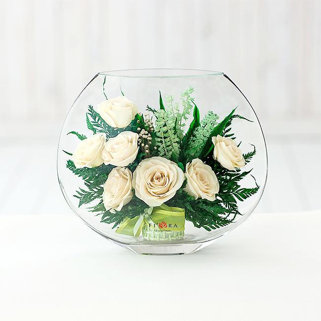 Композиции из искусственных цветов в круглых вазах, стоит букет белых